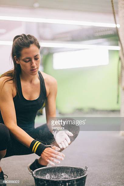 Woman adding gym chalk before a cross fitness session.