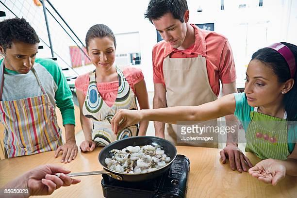 Woman adding ingredient to cooking shrimp