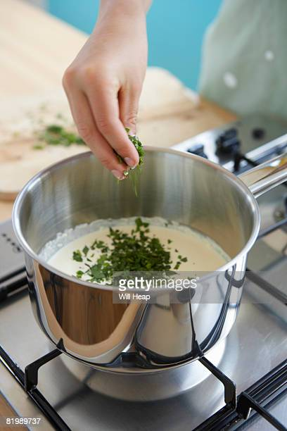 Woman adding mint to creamy sauce, close up