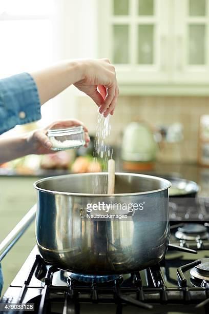 Mulher adicionando Aperte de sal na panela no Fogão de cozinha