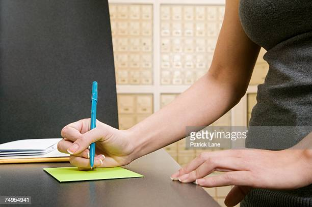 Woman addressing envelope