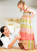 Woman adjusting a girl's dress