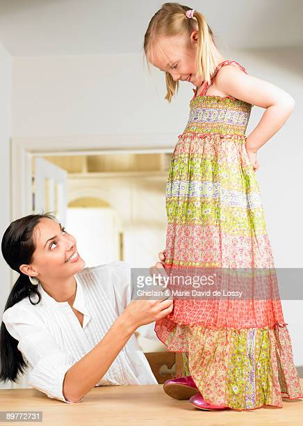 Woman adjusting a girl's dress