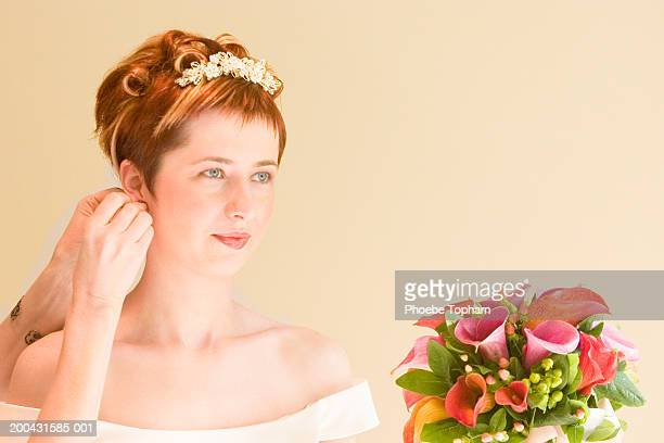 Woman adjusting bride's earring, bride looking away