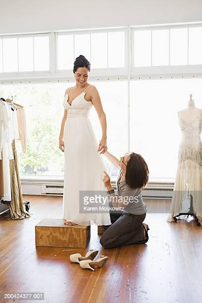 Woman adjusting bride's wedding dress during fitting