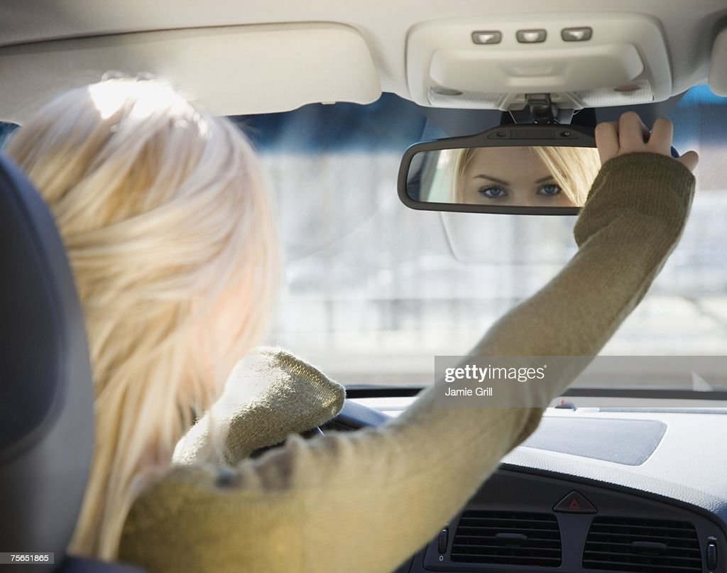 Car Rear View Mirror: Woman Adjusting Car Rear View Mirror Stock Photo