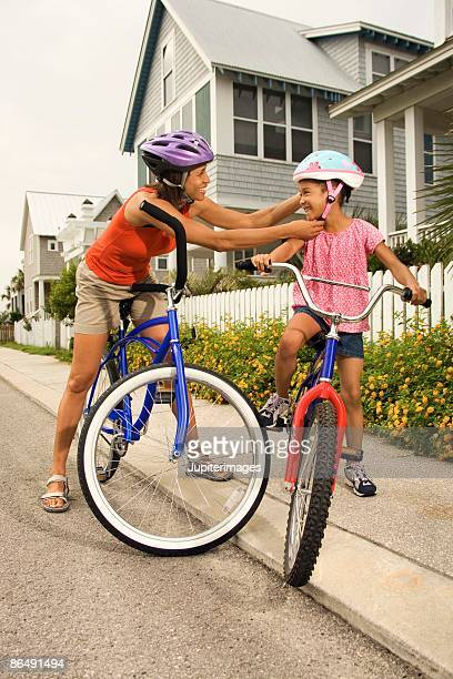 Woman adjusting daughter's safety helmet