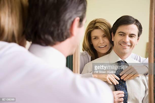 Woman adjusting husband?s necktie