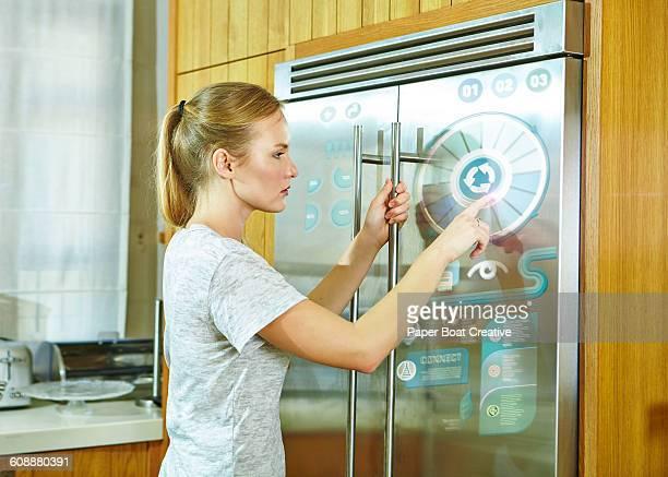 Woman adjusting settings on her modern fridge
