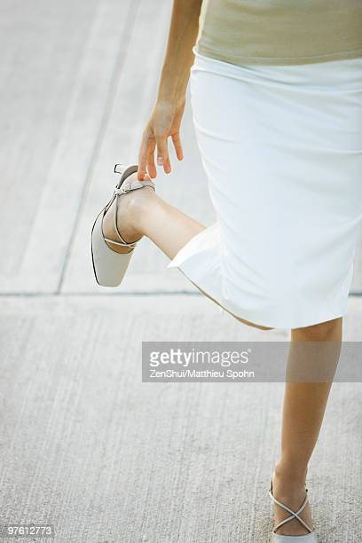 Woman adjusting strap on high heel shoes, low section