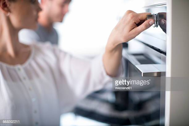 Woman adjusting temperature of oven