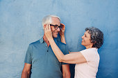 Portrait of woman adjusting the eyeglasses on her husband against blue background. Mature couple together on a blue wall.