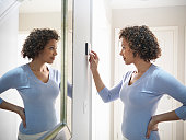 Woman adjusting thermostat in home