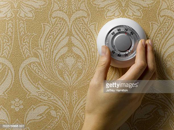 Woman adjusting thermostat on beige wallpapered wall, close-up