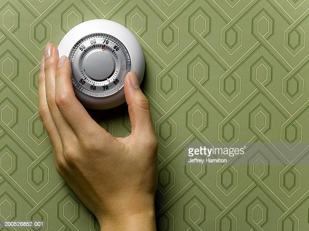 Woman adjusting thermostat on green wallpapered wall, close-up