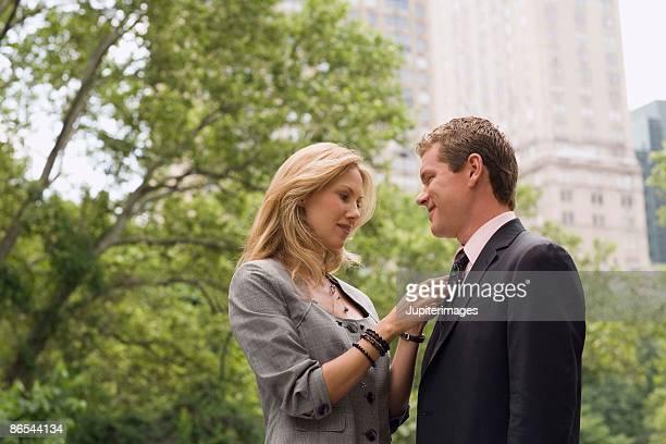Woman adjusting tie on man in park