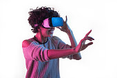 Young African woman smiling and touching air while having VR experience and adjusting goggles isolated on white.