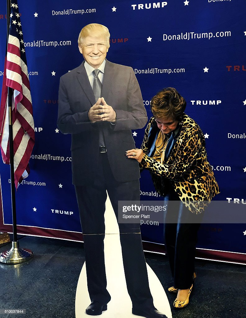 A woman adjusts a cardboard cutout of presidential candidate Donald Trump at his headquarters in Greenville on the day of the Republican Presidential debate on February 13, 2016 in Greenville, South Carolina. This evenings debate will see the six remaining candidates go at each other in a state known to reward more conservative candidates.
