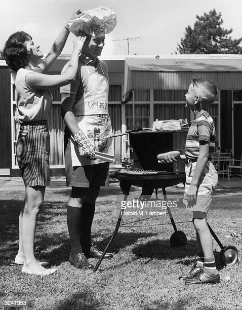 A woman adjusts a chef's hat on her husband who is standing at a grill as his son looks on holding a hot dog during a backyard barbecue The man wears...