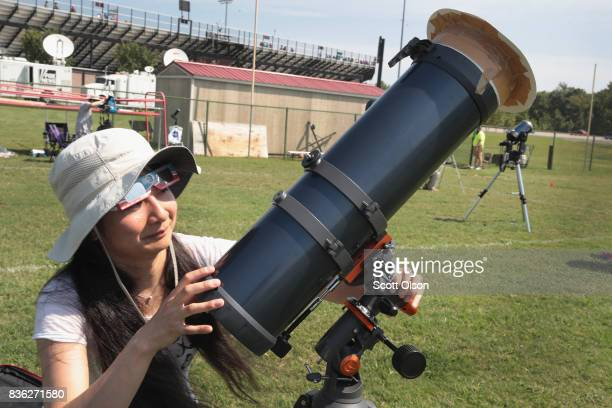 A woman adjusts a telescope before the total solar eclipse on the campus of Southern Illinois University on August 21 2017 in Carbondale Illinois...