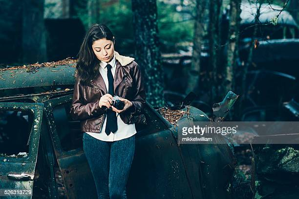 Woman adjusts an old camera at a junkyard