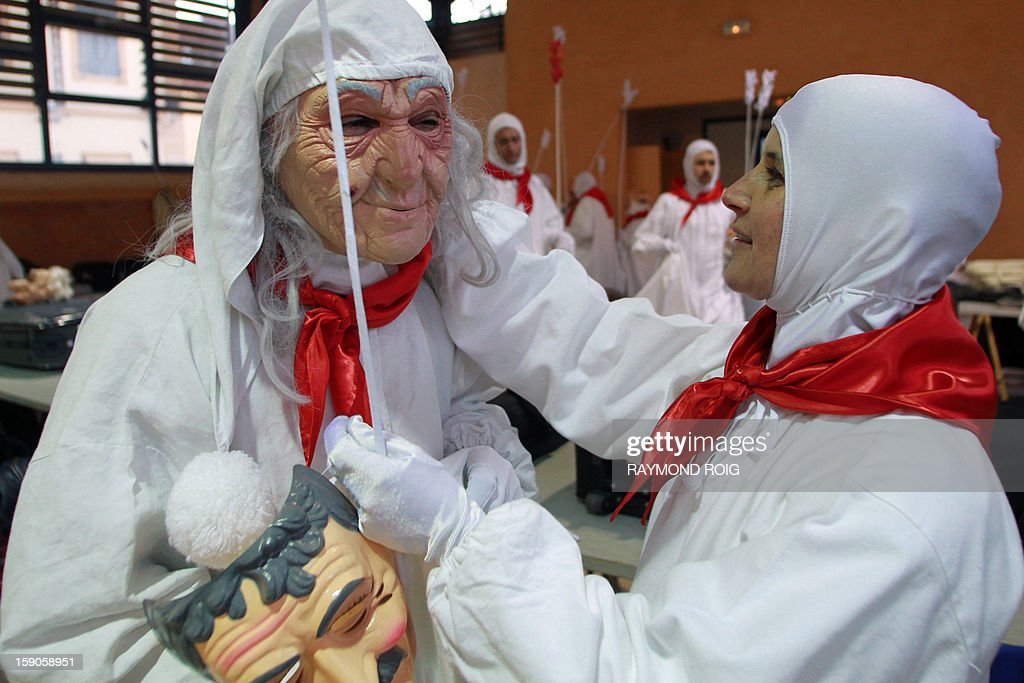 A woman adjusts another participant's mask in the historical centre of Limoux, southern France, on January 6, 2013, during the city's carnival, which started on January 6 and will end on March 17. AFP PHOTO / RAYMOND