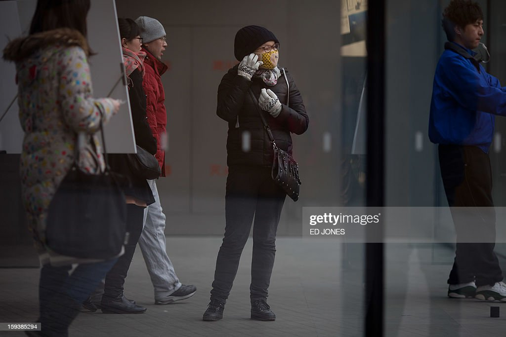 A woman adjusts her face mask before leaving a shop during polluted weather in Beijing on January 13, 2013. Dense smog shrouded Beijing, with pollution at hazardous levels for a second day and residents advised to stay indoors, state media said. AFP PHOTO / Ed Jones