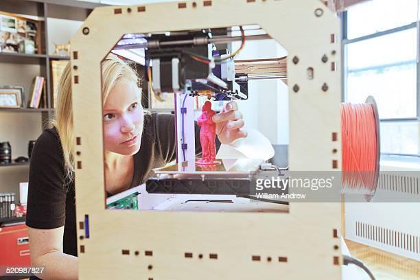 Woman adjusts print on 3D printer