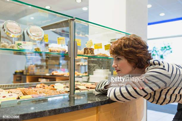 woman admire cakes at bakery counter