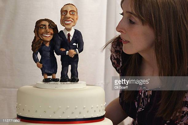 A woman admires a cake featuring figurines of Prince William and Kate Middleton at an exhibition of Royal Wedding cakes on April 21 2011 in London...