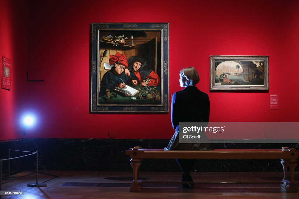 A woman admires a painting by a Follower of Marinus van Reymerswaele entitled 'The Misers' (L) in the exhibition 'The Northern Renaissance: Durer to Holbein' at The Queen's Gallery on October 29, 2012 in London, England. The exhibition, which celebrates the Renaissance in Northern Europe through work by some of the finest artists of the era, opens to the general public on November 2 and runs until April 14, 2013.