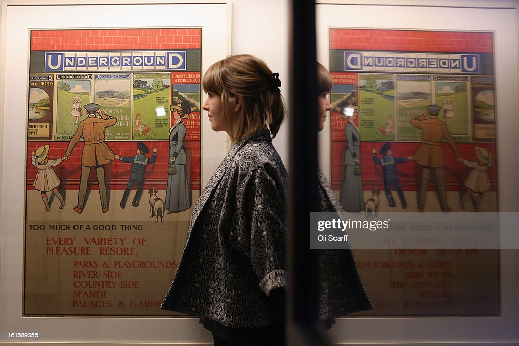 A woman admires a poster from 1910 entitled 'Too Much Of A Good Thing' by John Henry Lloyd in the exhibition 'Poster Art 150 - London Underground's Greatest Designs' in the London Transport Museum on February 12, 2013 in London, England. The exhibition celebrates 150 years of the London Underground by showcasing 150 posters from the Museum's archive of over 3,300. The exhibition opens on February 15, 2013 and runs until October 27, 2013.