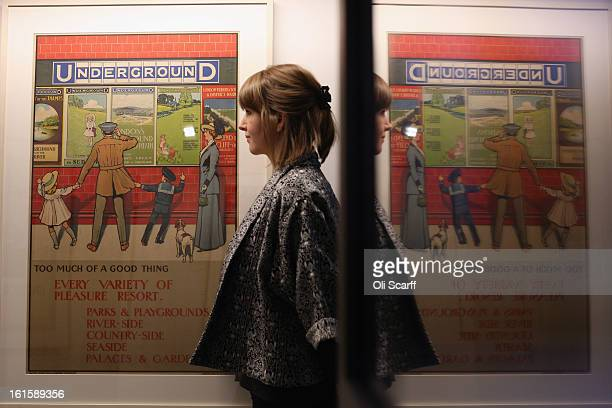 A woman admires a poster from 1910 entitled 'Too Much Of A Good Thing' by John Henry Lloyd in the exhibition 'Poster Art 150 London Underground's...