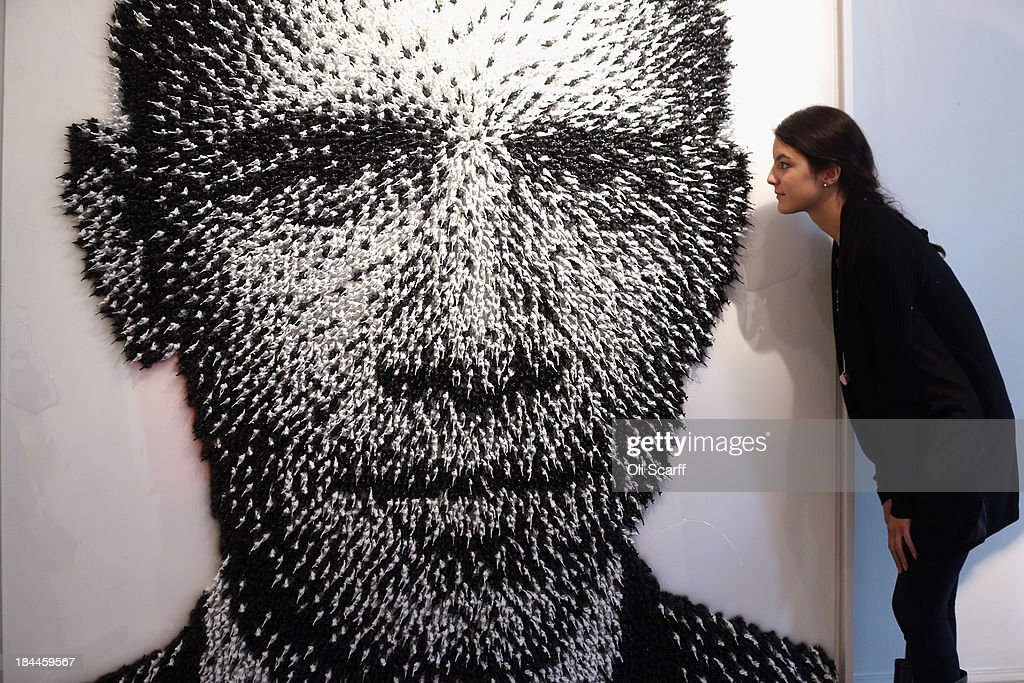 A woman admires an artwork by Joe Black of <a gi-track='captionPersonalityLinkClicked' href=/galleries/search?phrase=Barack+Obama&family=editorial&specificpeople=203260 ng-click='$event.stopPropagation()'>Barack Obama</a> entitled, 'Shoot to Kill', which is made from 11,000 hand-painted toy soldiers, in the Opera Gallery on October 14, 2013 in London, England. The Opera gallery is hosting contemporary artist Joe Black's first solo exhibition entitled 'Ways of Seeing', which opens to the public on October 18, 2013.