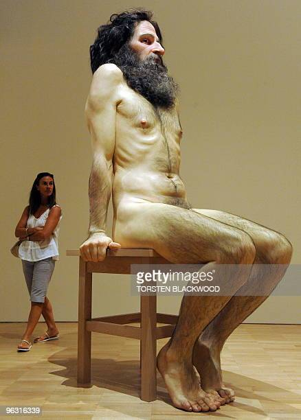 A woman admires the giant silicon and fibreglass scuplture 'Wild Man' by Australian artist Ron Mueck at the National Gallery of Victoria in Melbourne...