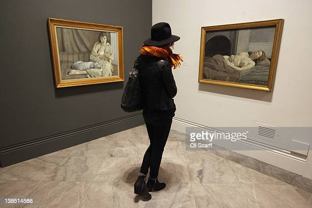 A woman admires the Lucian Freud paintings 'Girl with a White Dog' and 'Sleeping Nude' in the 'Lucian Freud Portraits' exhibition at the National...
