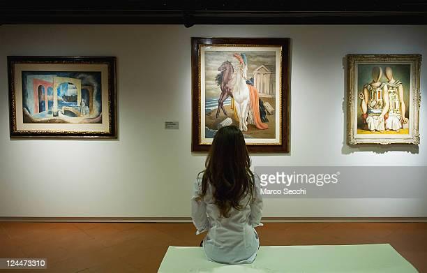 A woman admires the painting by Giorgio de Chirico 'Due Cavalli sulla Spiaggia' at the press opening of 'Dalla Figura Alla Figurazione Nel '900...