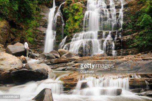 Woman admiring a beautiful waterfall : Stock Photo