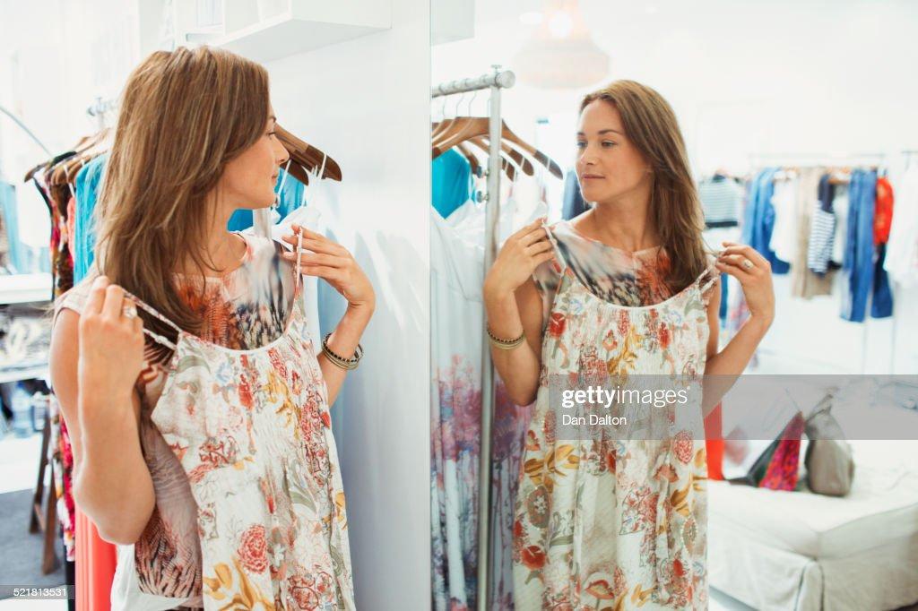 Woman admiring dress in store mirror