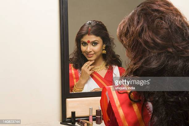 Woman admiring her beauty in front of a mirror