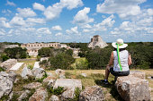 Woman admiring the Mayan ruins of Uxmal, Yucatan, Mexico.  She is sitting on a stone remant looking over the archaelogical site wearing a hat.