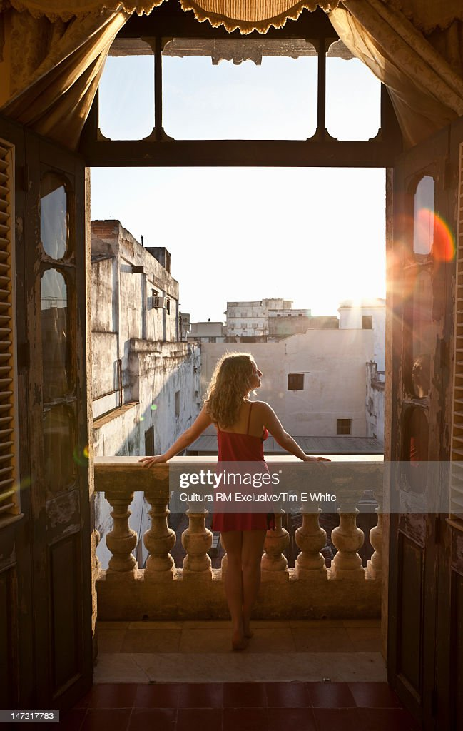 Woman admiring view from balcony : Stock Photo