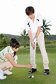 Woman advising man on putting green, Saipan, USA