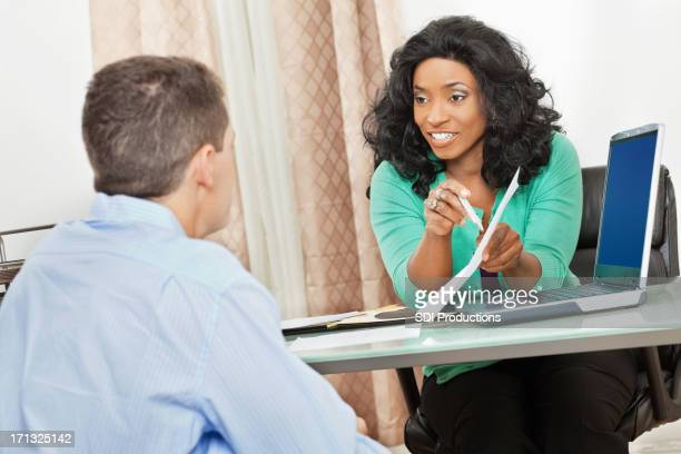 Woman advising man using charts and computer