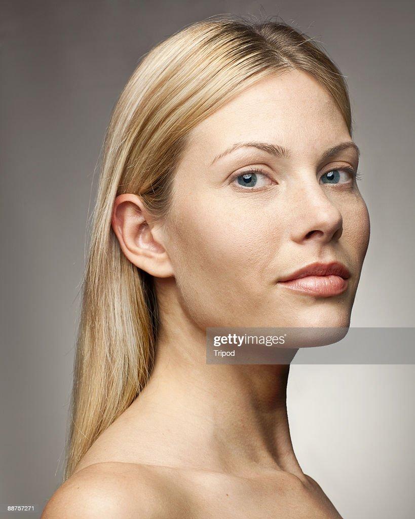 Woman against grey background, portrait : Stock Photo
