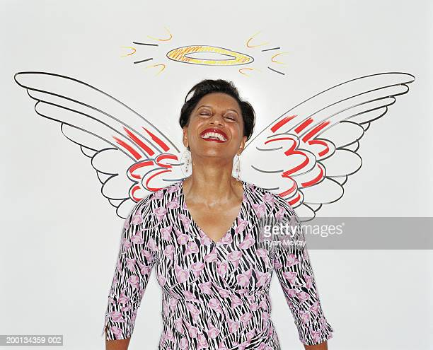 Woman against  wall illustrated with angel wings and halo
