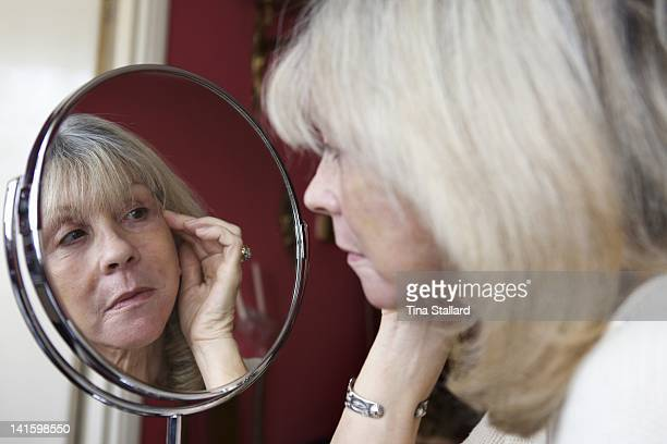 A woman aged 62 examines her face in the mirror three weeks after her facelift operation The scars on her eyelids are fading but her face is still...