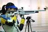 beautiful young woman aiming a pneumatic air rifle