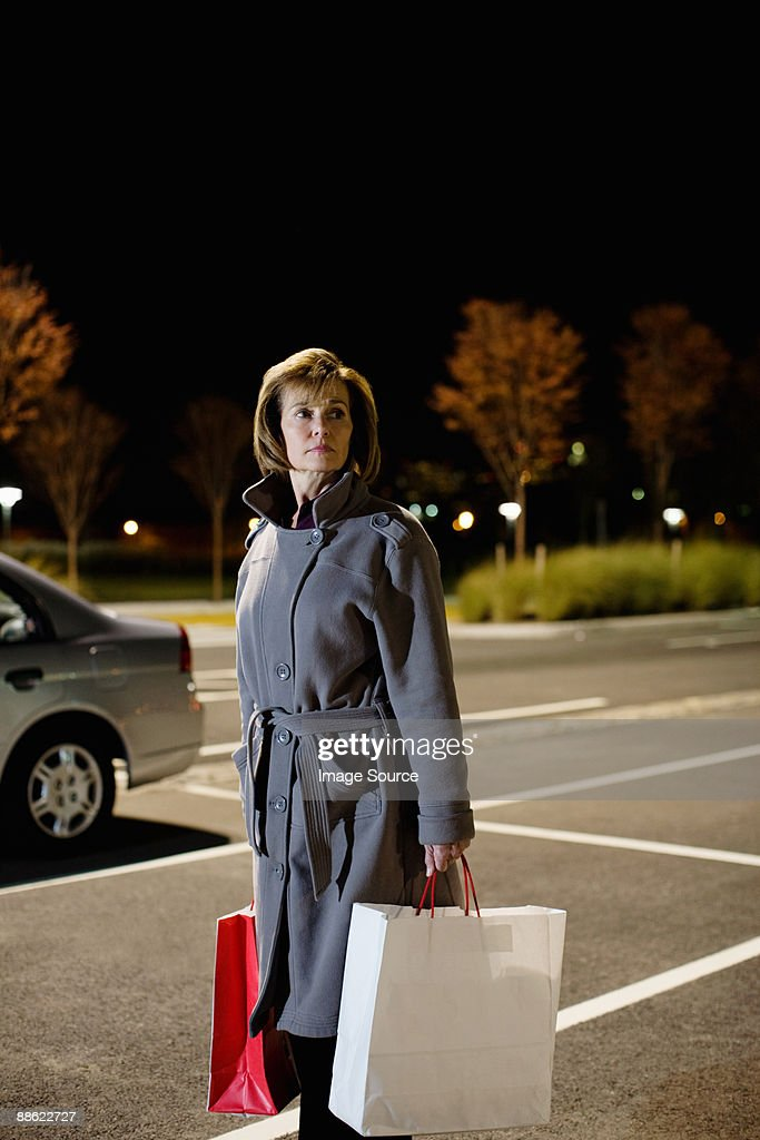 Woman alone in parking lot : Stock Photo