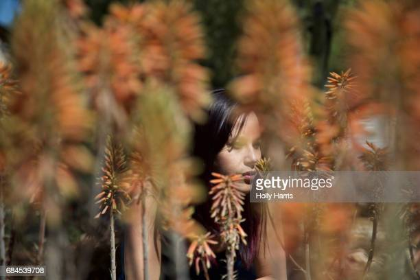 Woman amidst orange plants in desert garden